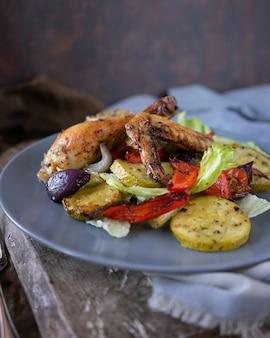 Pedaços assados caseiros de frango com ervas aromáticas e salada de legumes