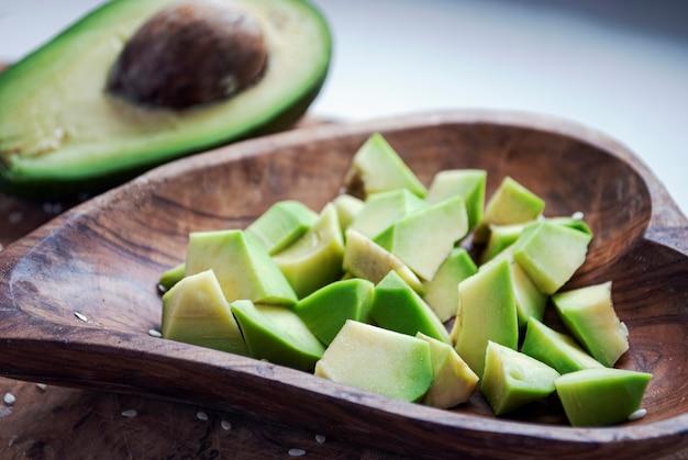Pedaços de abacate em um prato de madeira ao lado de meio abacate.