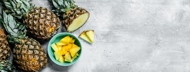 Pedaços de abacaxi fresco em uma tigela e abacaxis maduros. sobre fundo branco rústico