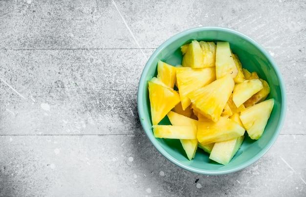 Pedaços de abacaxi maduro em uma tigela. sobre fundo branco rústico