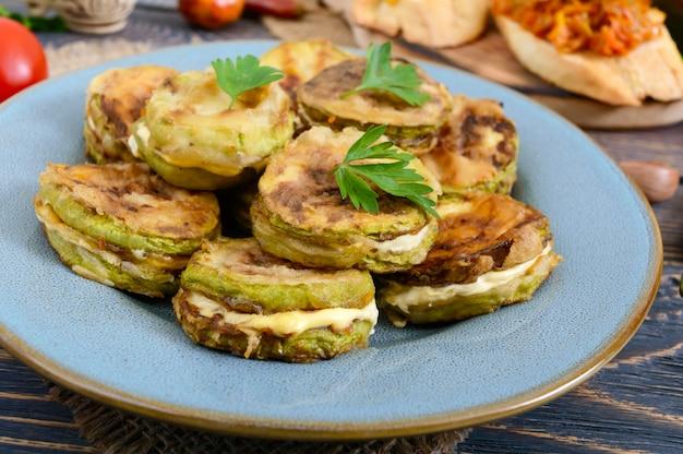 Pedaços de abobrinha fritos com maionese em um prato de cerâmico em uma mesa de madeira.