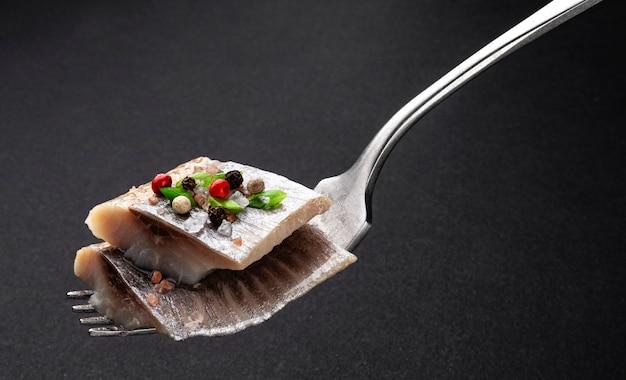 Pedaços de arenque salgado no garfo em preto, fatias de filete de peixe cavala defumado com sal e especiarias