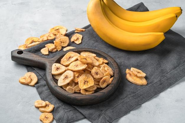 Pedaços de bananas secas e bananas frescas em um pano de cozinha cinza