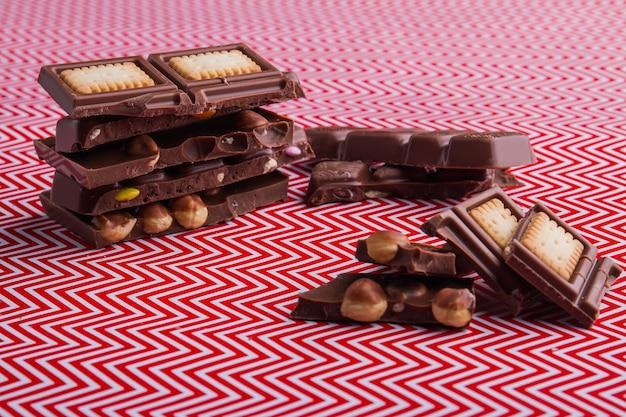 Pedaços de barra de chocolate com recheio de avelãs e biscoitos. sobremesa deliciosa e doce.