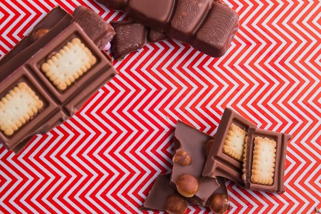Pedaços de barra de chocolate de vista superior com biscoitos grossos e avelãs. vista superior plana lay.