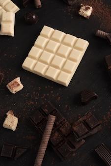 Pedaços de barra de chocolate e doces sobre a superfície de madeira