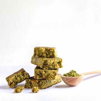 Pedaços de barra de granola com matcha e colher de pó