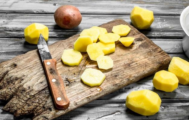Pedaços de batatas frescas em uma placa de corte com uma faca. em madeira