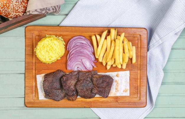 Pedaços de bife de carne com batatas fritas, cebola e arroz na placa de madeira.