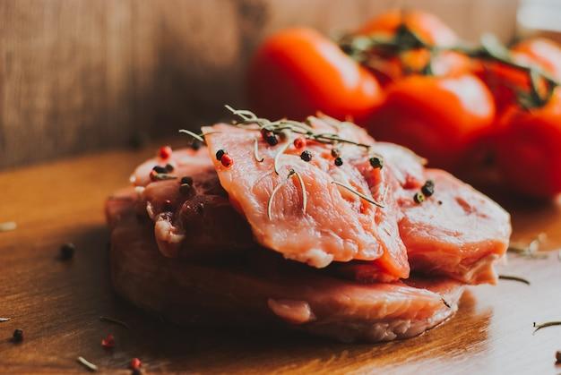 Pedaços de bife de carne de porco crua com especiarias e ervas alecrim, tomilho, manjericão, sal e pimenta