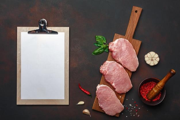 Pedaços de bife de carne de porco crua com manjericão, alho, pimenta, sal e especiaria argamassa e tablet na placa de corte e fundo marrom enferrujado com espaço para seu texto.