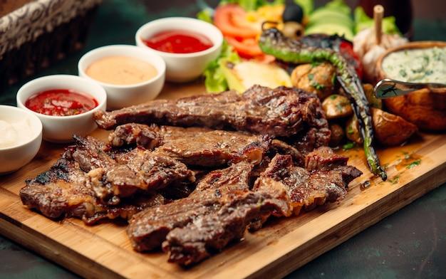 Pedaços de bife de cordeiro com molhos, pimenta grelhada, salada fresca na placa de madeira