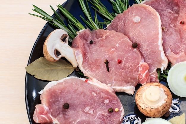 Pedaços de bife de porco cru com especiarias e ervas alecrim, cogumelos, cebola, folha de louro, sal e pimenta em uma placa preta e mesa de madeira branca, vista superior