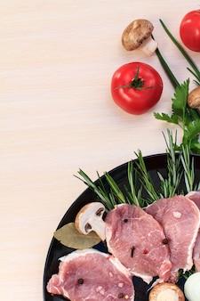 Pedaços de bife de porco cru com especiarias e ervas alecrim, cogumelos, tomate, cebola, salsa, folha de louro, sal e pimenta em um prato preto e mesa de madeira branca, vista superior