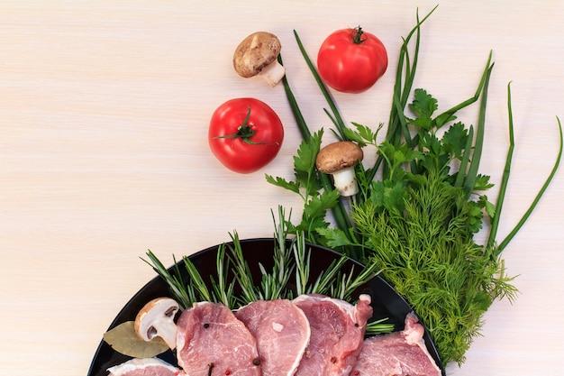 Pedaços de bife de porco cru com especiarias e ervas alecrim, cogumelos, tomate, sal e pimenta em uma placa preta e mesa de madeira branca, vista superior