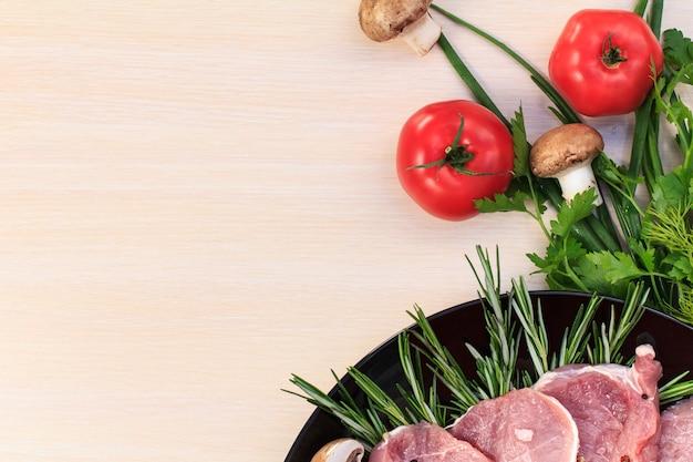 Pedaços de bife de porco cru com especiarias e ervas alecrim, cogumelos, tomate, salsa, endro, sal e pimenta em uma placa preta e mesa de madeira branca, vista superior