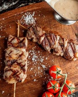 Pedaços de bife grelhado no espeto de bambu, guarnecido com sal e tomate