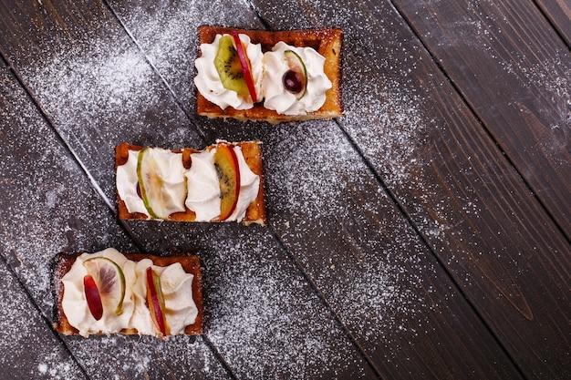 Pedaços de bolo com frutas cobertas com açúcar em pó, servido em uma mesa de madeira