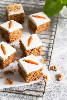 Pedaços de bolo de cenoura com nozes com creme de confeiteiro sobre um fundo claro.
