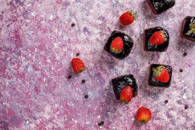 Pedaços de bolo de chocolate com calda de chocolate e com frutas.