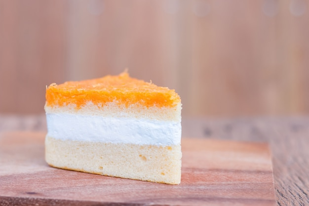 Pedaços de bolo de laranja, fios dourados na mesa de madeira