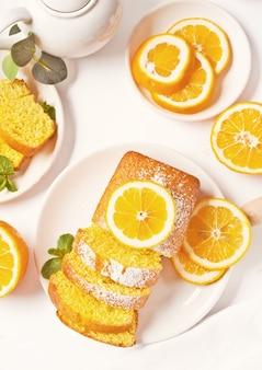 Pedaços de bolo de limão fatiado caseiro fresco no prato branco.