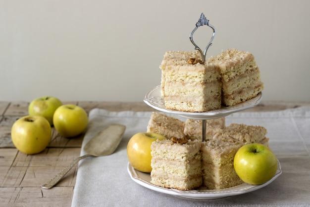 Pedaços de bolo de maçã e maçãs em uma mesa de madeira. estilo rústico.