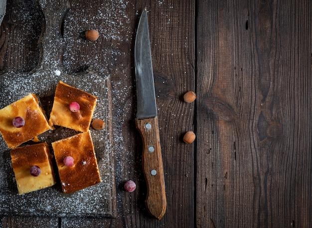 Pedaços de bolo de queijo com abóbora na tábua de madeira marrom