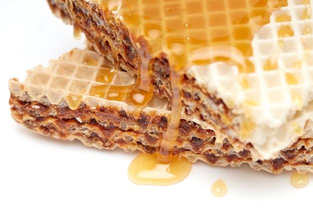 Pedaços de bolo waffle derramados com close up de mel em um fundo branco e isolado
