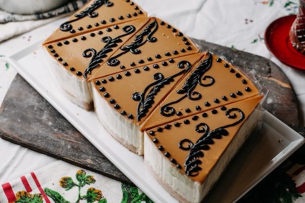 Pedaços de bolos fatiados marrom projetado creme gostoso delicioso dentro da placa branca no chá quente de mesa colorida