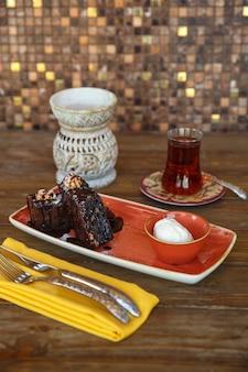 Pedaços de brownie com sorvete de baunilha, servidos com chá preto