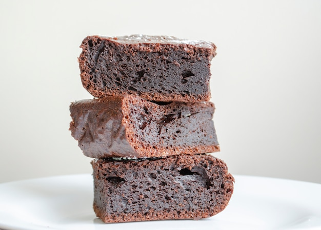 Pedaços de brownie de bolo de chocolate sobre um fundo claro. sobremesa americana de chocolate gostoso caseiro.