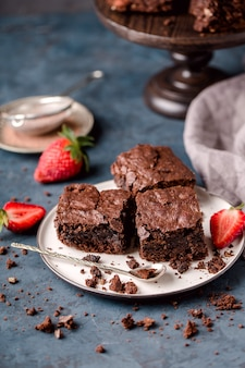 Pedaços de brownie de chocolate, no prato branco, colher, com fatias de morangos, migalhas, têxteis cinza. fundo azul escuro. vertical