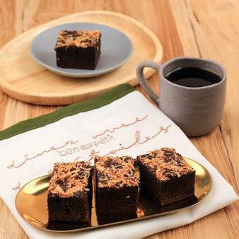 Pedaços de brownie fresco com queijo ralado por cima. deliciosa torta de chocolate, servida com uma xícara de café na mesa de madeira