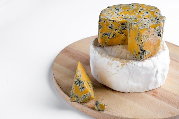 Pedaços de camembert e queijo azul de shropshire em uma placa de madeira