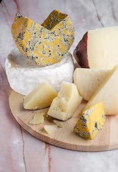 Pedaços de camembert, parmesão e queijo azul de shropshire em uma placa de madeira