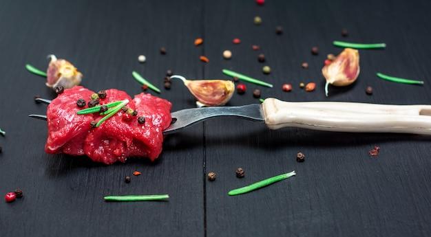 Pedaços de carne amarrado em um garfo de cozinha