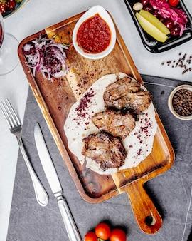 Pedaços de carne assada em uma placa de madeira