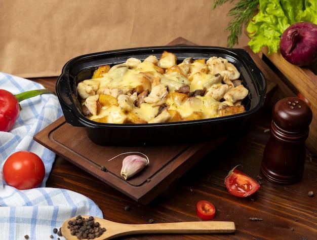 Pedaços de carne assada grelhada e fatias de batata em creme derretido queijo, molho de manteiga takeaway