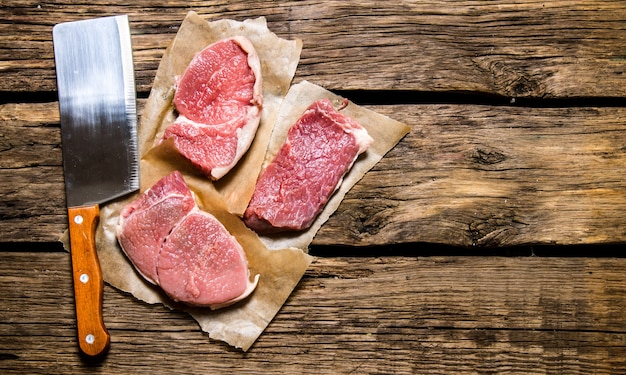 Pedaços de carne crua com uma faca de açougueiro. em fundo de madeira. espaço livre para texto. vista do topo