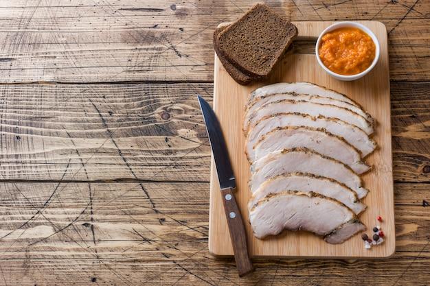 Pedaços de carne de porco cozida defumada em uma placa de madeira rústica
