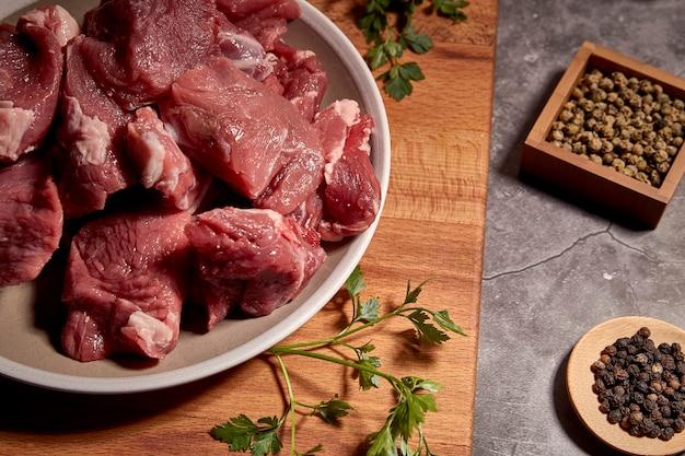 Pedaços de carne de vitela vermelha em uma placa de madeira e ao lado de diferentes especiarias