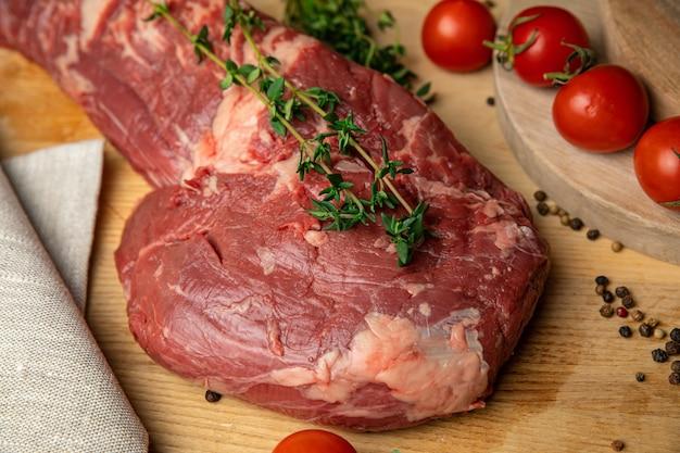 Pedaços de carne fatiada de carne crua com especiarias e ervas em uma placa de madeira