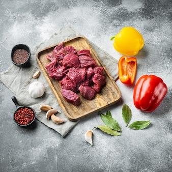 Pedaços de carne fresca servidos na mesa com ingredientes prontos para cozinhar