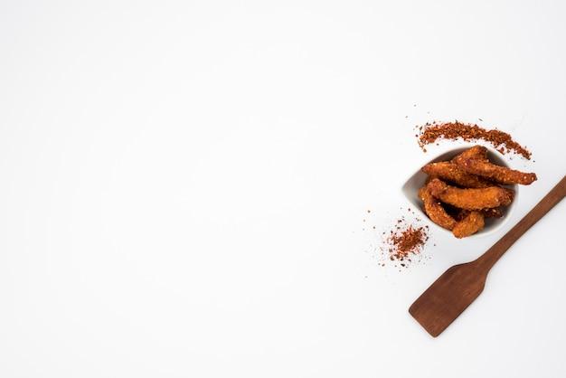 Pedaços de carne frita com especiarias e espátula na mesa cinza