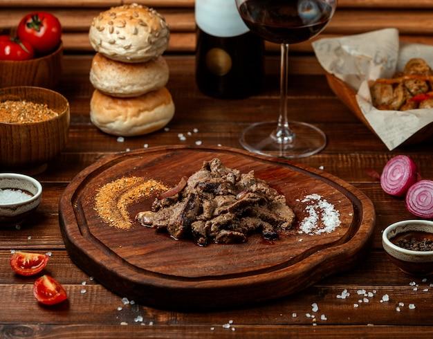 Pedaços de carne frita na placa de madeira