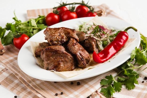 Pedaços de carne grelhados em um prato branco com ervas e legumes