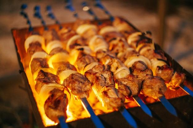 Pedaços de carne são amigos pegando fogo em espetos na grelha de perto