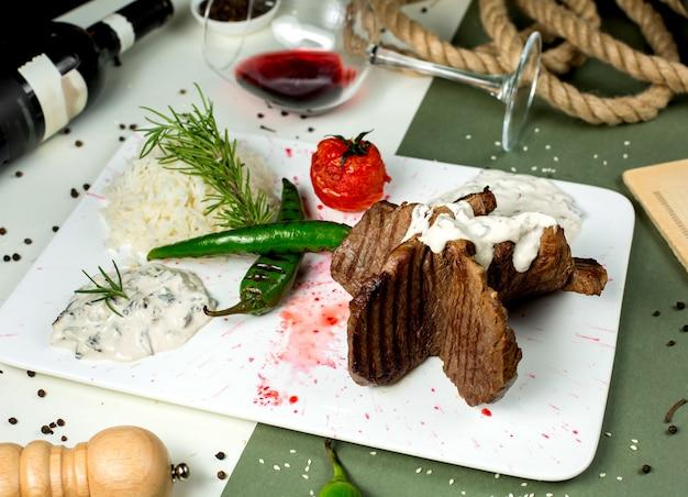 Pedaços de carne servidos com arroz cremoso de molho de cogumelos e legumes grelhados