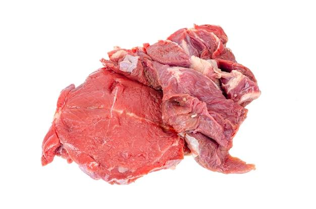 Pedaços de carne vermelha fresca, isolada na mesa branca.